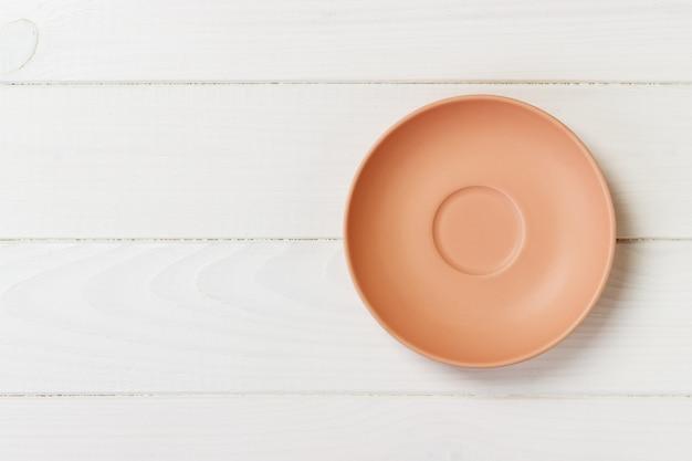 Vista superiore del piatto rotondo arancio su un fondo di vecchia plancia di legno della tavola. piatto rotondo opaco
