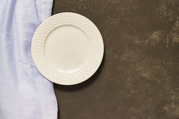 Vista superiore del piatto servito vuoto, tessuto blu su calcestruzzo nero