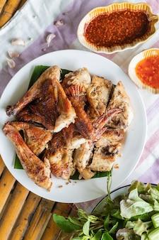 Vista superiore del pollo alla griglia in zolla bianca su priorità bassa di bambù