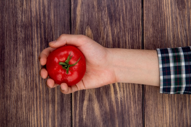Vista superiore del pomodoro della tenuta della mano della donna su superficie di legno