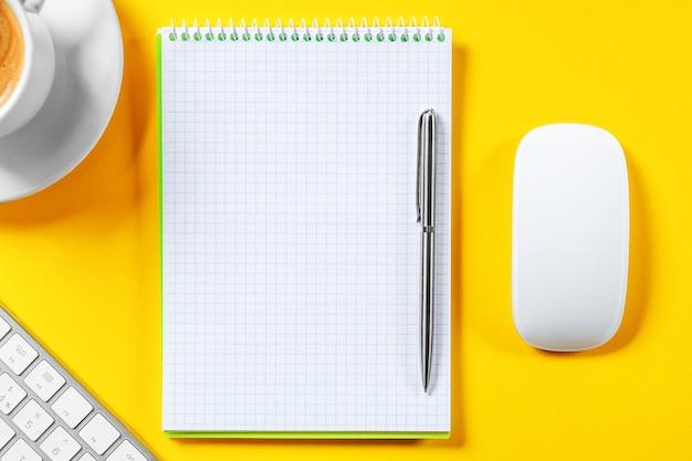 Vista superiore del posto di lavoro di affari con la tazza di caffè, area di lavoro vuota sulla tavola gialla.