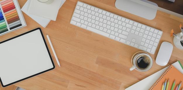 Vista superiore del posto di lavoro moderno con la compressa dello schermo in bianco e articoli per ufficio sulla tavola di legno