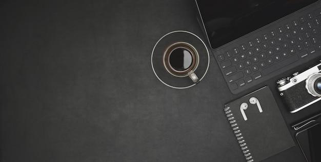 Vista superiore del posto di lavoro moderno scuro con tablet, tazza di caffè e articoli per ufficio sulla scrivania nera