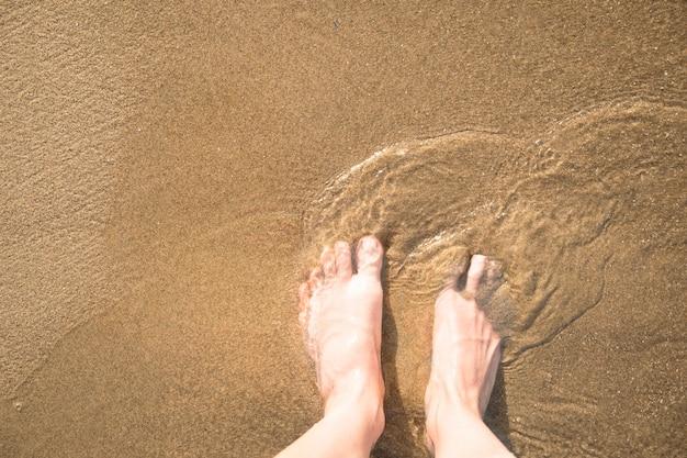 Vista superiore del primo piano dei piedi nella sabbia bagnata