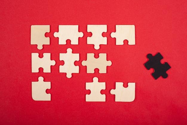 Vista superiore del primo piano di colore bianco e nero di puzzle. la guida alla leadership non rientra nella comunità dell'emarginato emarginato antisociale.
