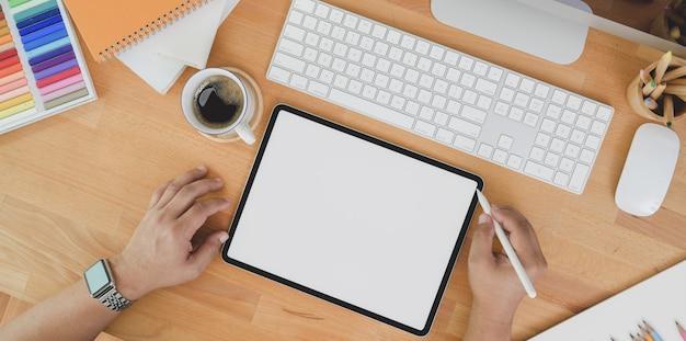Vista superiore del progettista professionista che pubblica il suo lavoro sul tablet sulla tavola di legno