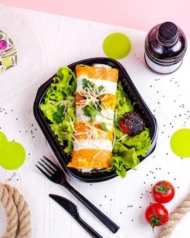 Vista superiore del rotolo del pancake con le verdure e il formaggio del pollo su lattuga in una scatola di consegna