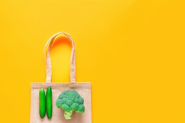 Vista superiore del sacchetto della spesa riutilizzabile del tessuto con le verdure verdi fresche su fondo giallo