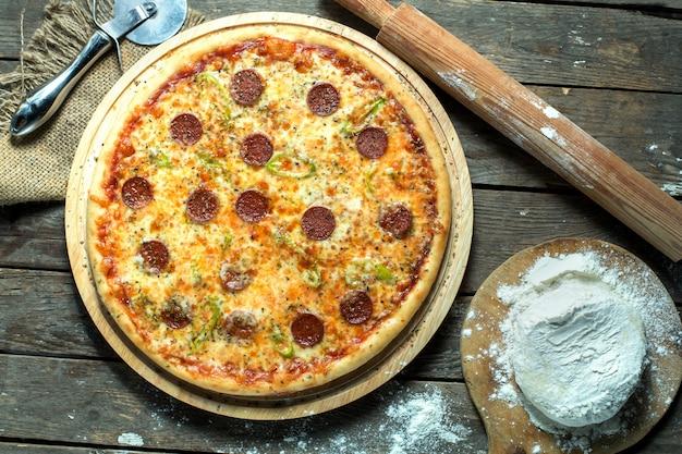 Vista superiore del salame della pizza con il peperoncino e le spezie verdi della salsa al pomodoro