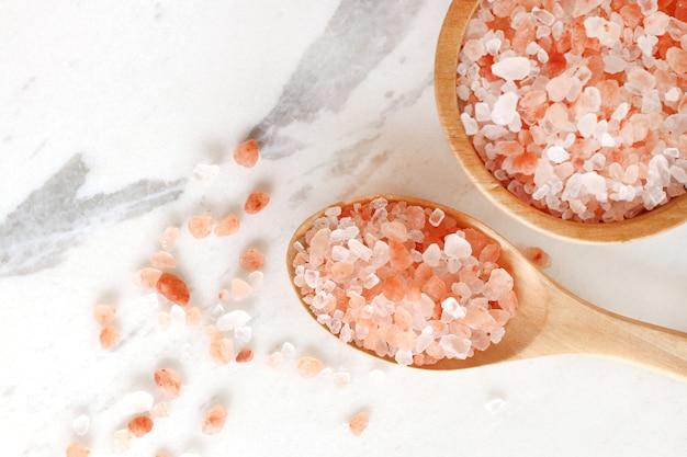 Vista superiore del salgemma rosa himalayano in ciotola e cucchiaio di legno sulla tavola di marmo bianca.