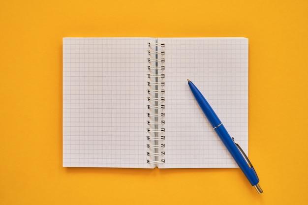 Vista superiore del taccuino aperto con pagine bianche e penna blu, quaderno di scuola su uno sfondo giallo, blocco note a spirale