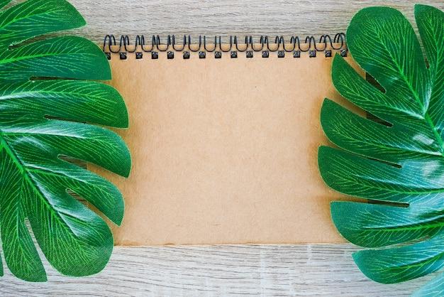 Vista superiore del taccuino aperto in bianco sul fondo di legno dello scrittorio con le foglie tropicali verdi di monstera.