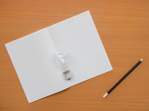 Vista superiore del taccuino, della lampadina e della matita sulla tavola di legno con lo spazio della copia