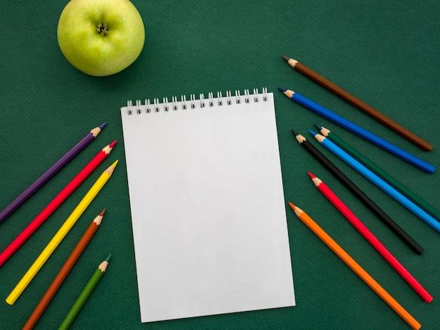 Vista superiore del taccuino in bianco, delle matite colorate e della mela verde