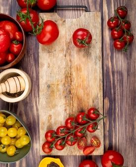 Vista superiore del taglio e dei pomodori interi sul tagliere con altri un frantoio dell'aglio del pepe nero su superficie di legno