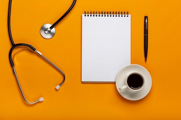 Vista superiore del tavolo scrivania del medico con lo stetoscopio, caffè e carta bianca su appunti con penna