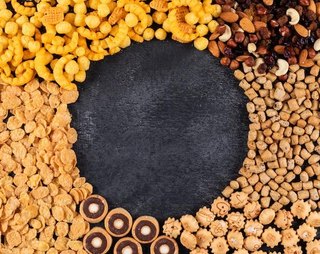 Vista superiore del tipo differente di spuntini come dadi, cracker e biscotti con lo spazio della copia sull'orizzontale scuro del fondo