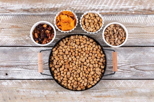 Vista superiore del tipo differente di spuntini come dadi, cracker e biscotti in ciotole sull'orizzontale di superficie di legno bianco