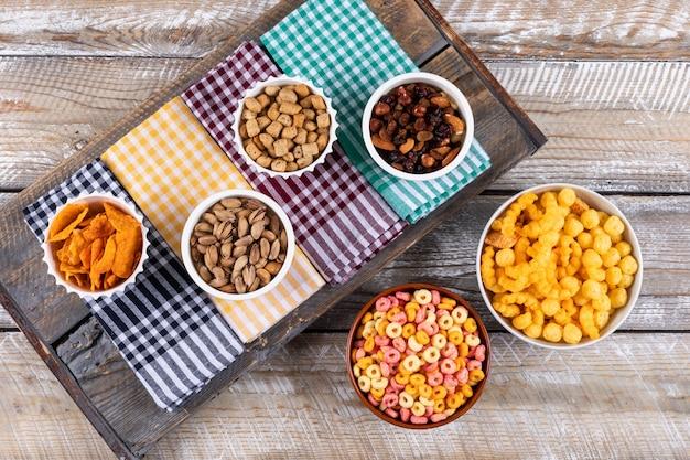 Vista superiore del tipo differente di spuntini come dadi, cracker e biscotti sui tovaglioli sull'orizzontale di superficie di legno bianco