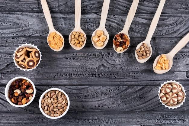 Vista superiore del tipo differente di spuntini come dadi e cracker sui cucchiai e sui biscotti di legno in ciotole con lo spazio della copia sull'orizzontale di superficie di buio