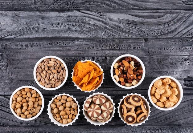 Vista superiore del tipo differente di spuntini come noci, cracker e biscotti in ciotole con lo spazio della copia sull'orizzontale di superficie di buio