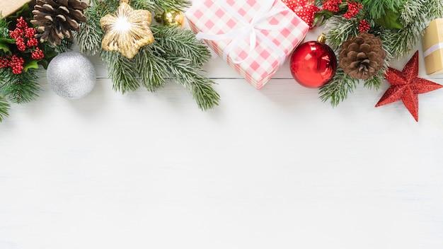 Vista superiore dell'albero di natale e del contenitore di regalo di feste del nuovo anno e di natale con l'ornamento decorativo sul fondo di legno bianco della tavola concetto del fondo dell'insegna di congratulazioni e dei regali con lo spazio della copia.