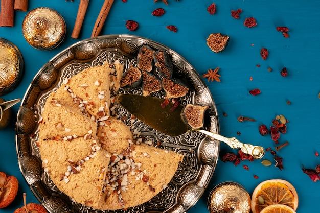 Vista superiore dell'assortimento di baklava turca sul piatto tradizionale su fondo scuro