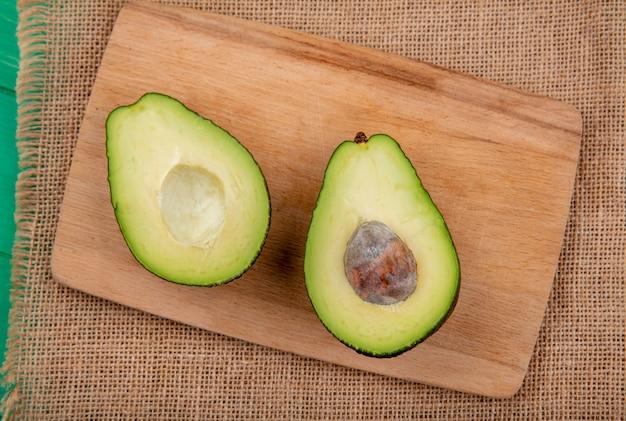 Vista superiore dell'avocado diviso in due sano e fresco su un bordo di legno della cucina sulla superficie del panno di sacco