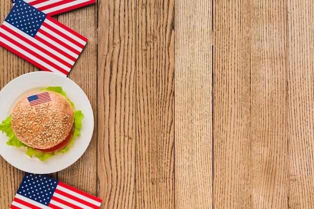 Vista superiore dell'hamburger sul piatto con le bandiere americane su superficie di legno e spazio della copia