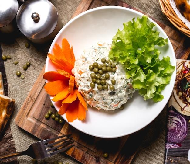 Vista superiore dell'insalata dell'oliva guarnita con i fiori e la lattuga della carota