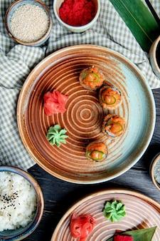 Vista superiore dell'insieme dei rotoli di sushi al forno con wasabi e lo zenzero su un piatto