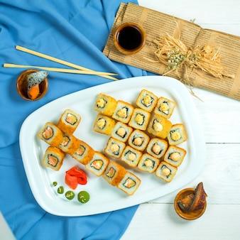 Vista superiore dell'insieme di cucina giapponese tradizionale del rotolo di sushi con i gamberi di color salmone avocado e crema di formaggio su blu e bianco