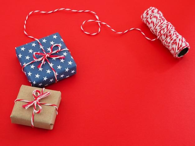 Vista superiore dell'involucro di carta del pacchetto del contenitore di regalo con il motivo a stelle e la corda su fondo rosso.