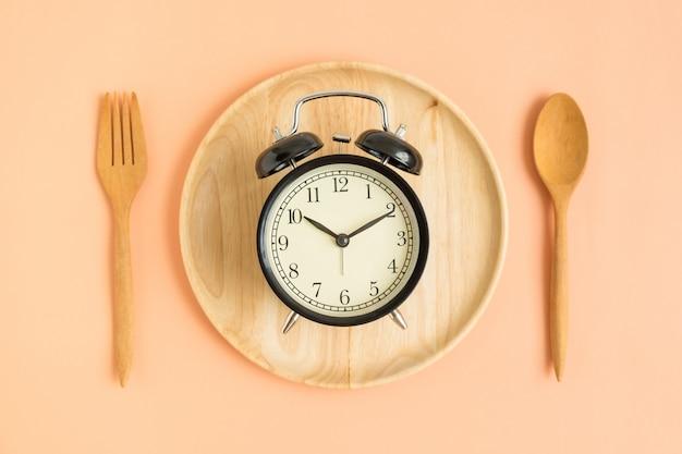 Vista superiore dell'orologio d'annata sul piatto di legno