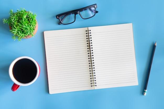 Vista superiore dell'ufficio blu pastello dello scrittorio con lo spazio della copia per input il testo