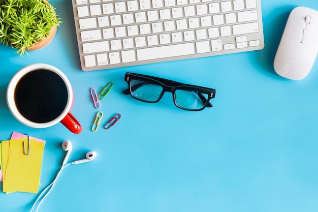 Vista superiore dell'ufficio blu pastello dello scrittorio con lo spazio della copia per input il testo.