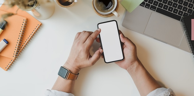 Vista superiore dell'uomo che tiene lo smartphone dello schermo in bianco nel posto di lavoro minimo