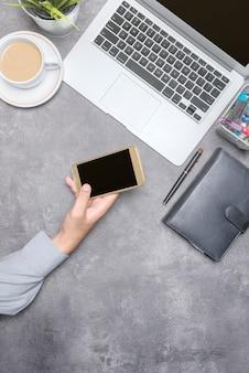 Vista superiore dell'uomo d'affari che per mezzo del telefono cellulare con gli accessori del computer portatile, del caffè, della pianta in vaso, del taccuino e di affari