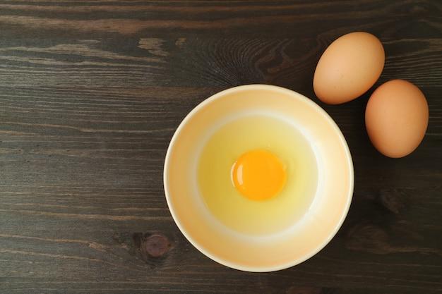 Vista superiore dell'uovo crudo fresco in una ciotola sulla tavola di legno