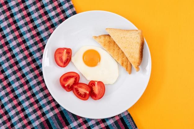 Vista superiore dell'uovo fritto con i pani tostati e il pomodoro sul piatto bianco e sull'orizzontale di superficie giallo