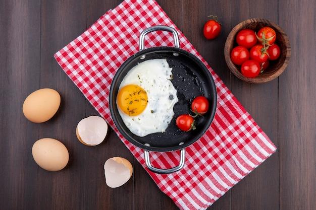 Vista superiore dell'uovo fritto con i pomodori in pentola sul panno del plaid e le uova con le coperture e la ciotola di pomodoro su superficie di legno