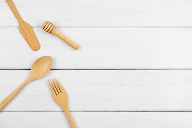 Vista superiore dell'utensile di legno della cucina sulla tavola di legno bianca