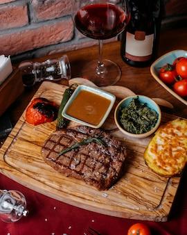 Vista superiore della bistecca di manzo alla griglia con patate nude e salsa su una tavola di legno