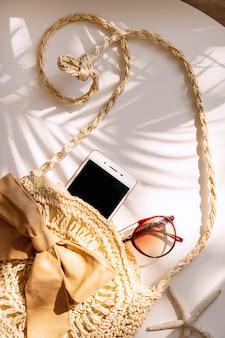 Vista superiore della borsa, dello smart phone e degli occhiali da sole di estate sulla parete bianca di colore, concetto di viaggio. disteso, copia spazio