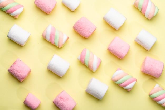 Vista superiore della caramella gommosa e molle rosa e bianca su giallo