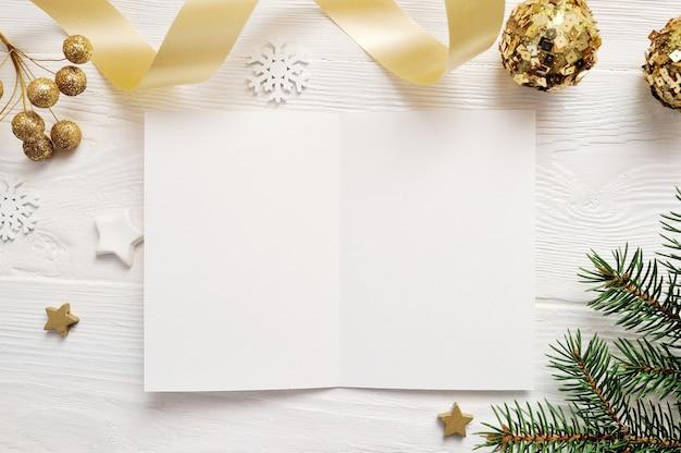 Vista superiore della cartolina d'auguri di natale e stella d'oro, flatlay su priorità bassa bianca