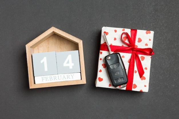 Vista superiore della chiave dell'automobile su un contenitore di regalo con i cuori rossi e il calendario festivo