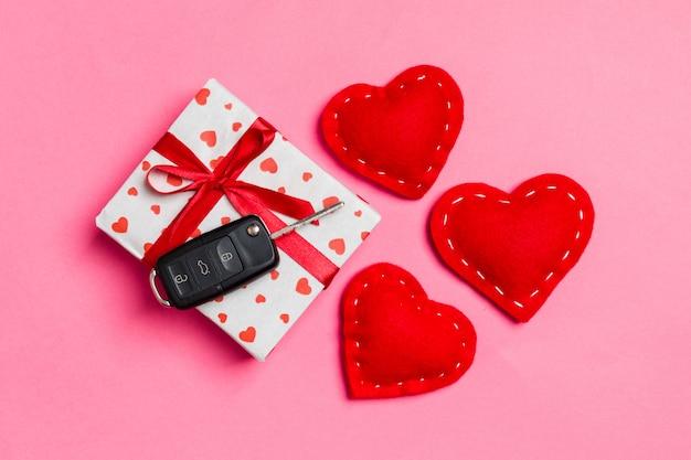Vista superiore della chiave dell'automobile sul contenitore di regalo e sui cuori rossi del tessuto