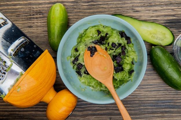 Vista superiore della ciotola di insalata di verdure con il cucchiaio di legno e cetrioli con la grattugia su superficie di legno