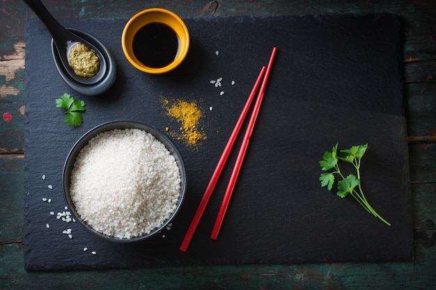 Vista superiore della ciotola di riso accanto bacchette rosse